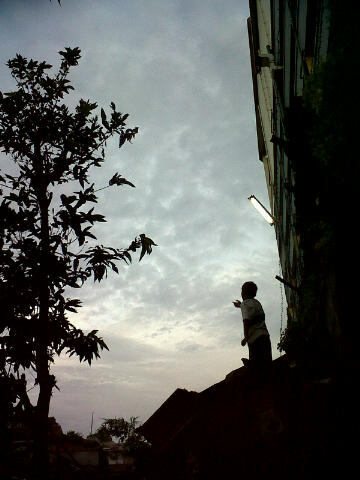 a pict of a boy playin a kite, taken while having a walk with my boyfriend in the streets of Bandung